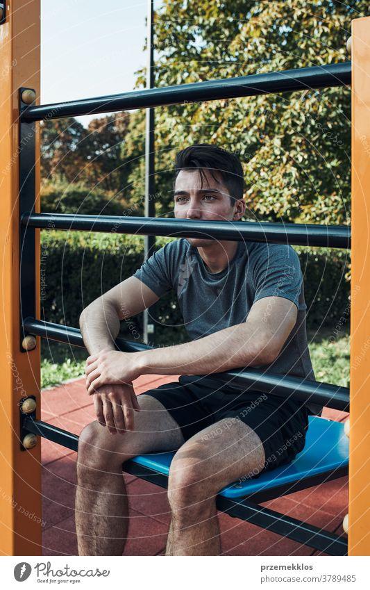 Porträt eines jungen Mannes, der während seines Trainings eine Pause in einem modernen Fitnesspark macht calisthenics Pflege Kaukasier Gesundheit Lifestyle