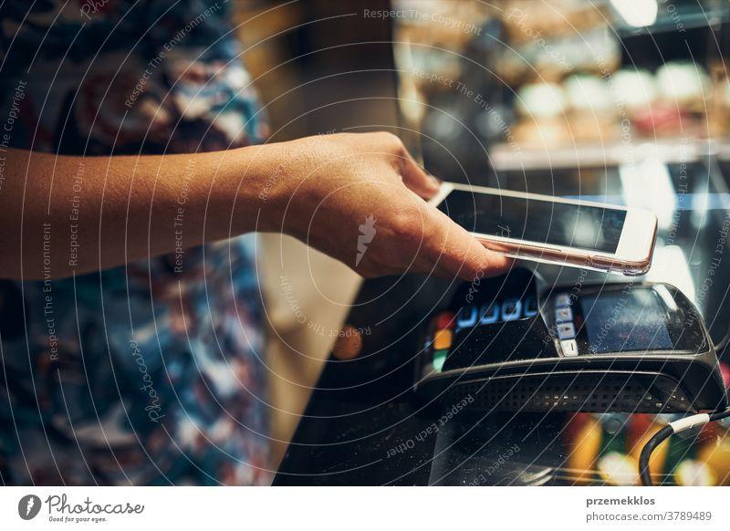 Frau bezahlt im Coffeeshop mit kontaktloser Zahlungsweise per Mobiltelefon Erwachsener kaufen Pflege Verbraucher berührungslos Kunde Gerät elektronisch
