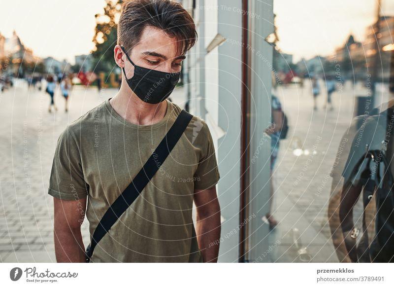 Junger Mann geht an einer Ladenfront im Stadtzentrum entlang und trägt die Gesichtsmaske, um eine Virusinfektion zu vermeiden Kaukasier Gespräch covid-19