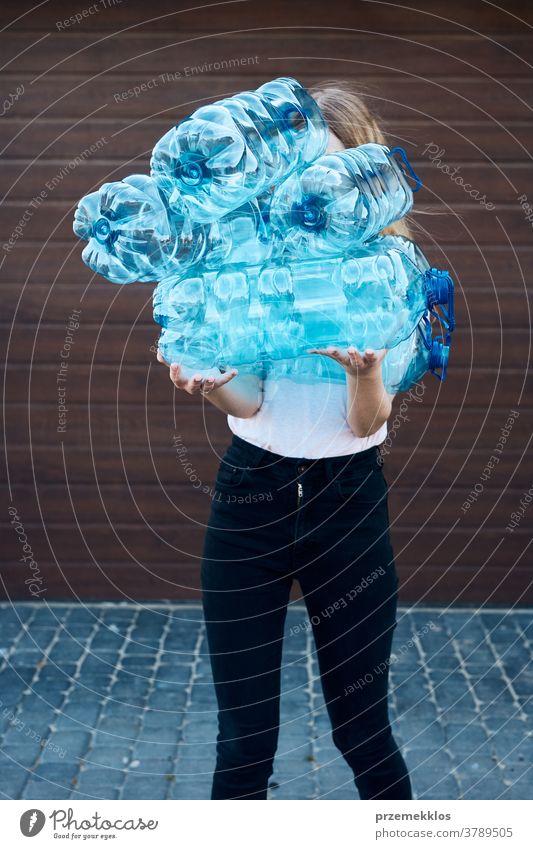 Junge Frau wirft leere gebrauchte Plastik-Wasserflaschen in den Mülleimer Behälter blau Flasche abholen sammelnd Container zerdrückt Entsorgung Ökologie Umwelt