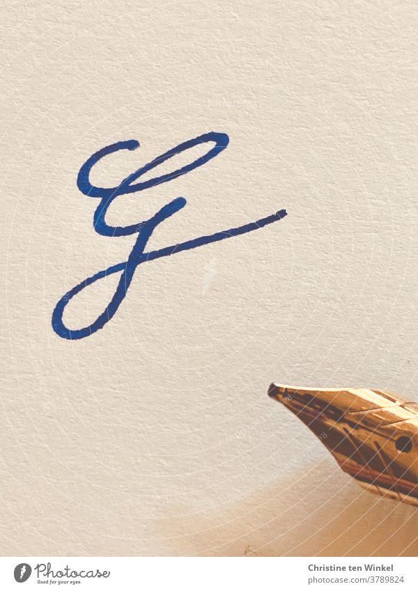 Der verschnörkelte Buchstabe G  auf hellem strukturiertem Papier, geschrieben mit blauer Tinte. Am rechten Bildrand sieht  man die goldfarbene Spitze des Füllfederhalters