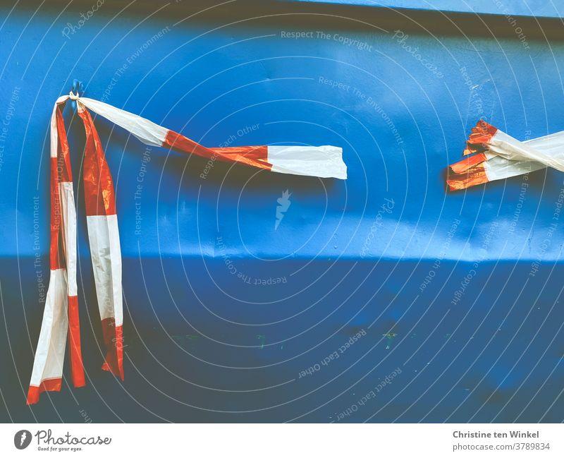 Gefangen in Plastik | An einem zerkratzen und verbeulten blauen Container aus Metall hängt zerrissenes rot und weiß gestreiftes Absperrband / Flatterband aus Kunststoff