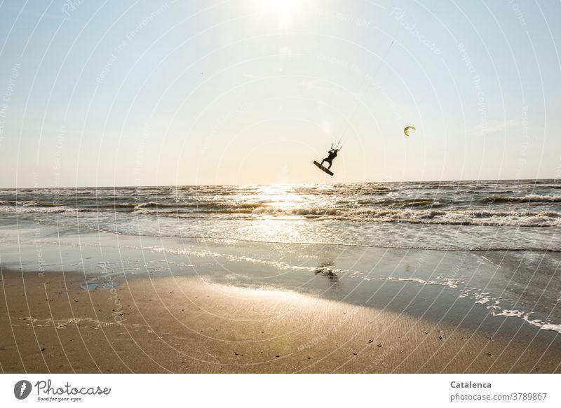 Kiter am Strand erhebt sich aus dem Wasser in die Luft Blau Sand Sandstrand Kitesurfen Urlaub Sport Meer Horizont Himmel Nordsee Wellen Brandung Küste Sonne