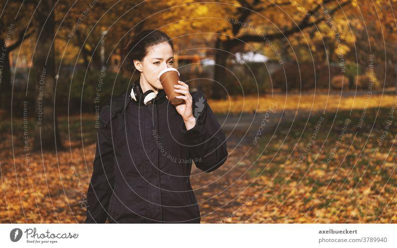 junge Frau, die unterwegs Kaffee zum Mitnehmen trinkt Hipster Lifestyle coffee to go trinken Menschen im Freien echte Menschen Herbst Getränk Park Mädchen