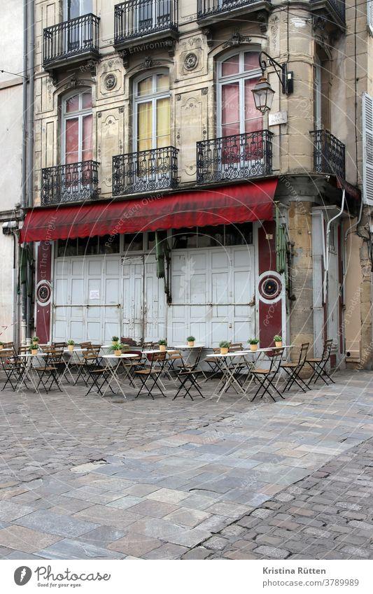 terrasse von noch nicht geöffnetem café tische stühle cafe restaurant brasserie bistro bar gastronomie draußen außengastronomie stadt urban straße platz haus
