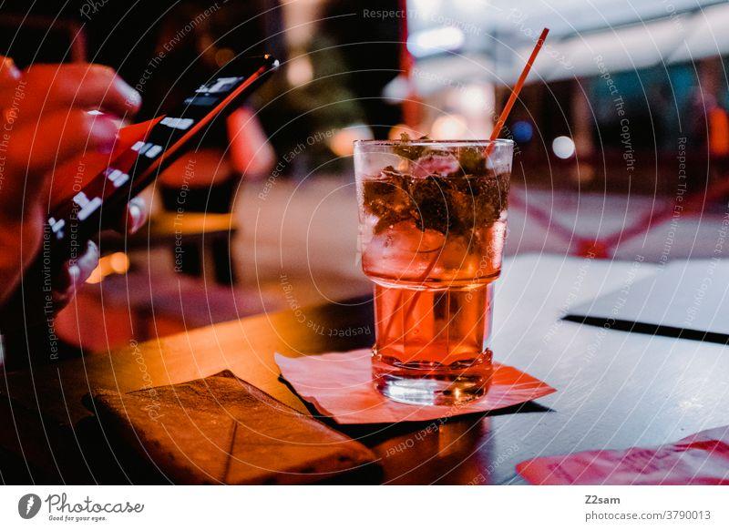 Junge Frau mit Smartphone und Cocktail in einer Bar gardasee Urlaub trinken getränk ausgehen Alkohol warten verabredet Cocktailbar Glas Getränk