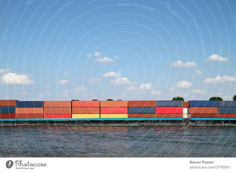 Frachtschiff mit zahlreichen bunten Containern auf einem Fluss blau Business Ladung wirtschaftlich Kranich Versand Dock Export Ware hafen importieren