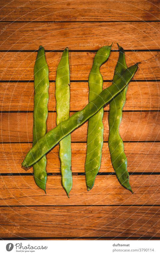Fünf grüne Bohnen liegen auf Holztisch zählen Stangenbohnen fünf Ernährung Makroaufnahme Strukturen & Formen 5 struktur abstreichen Vegetarische Ernährung