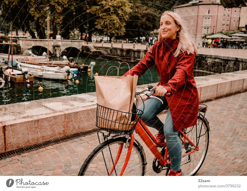 Junge Frau fährt mit dem Fahrrad durch Riva del Garda gardasee norditalien bombig Stadt mobilität Bewegung kaufen einkaufen italienisch Hafen Regeneration