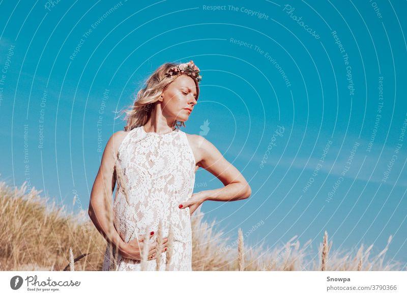 Junge, blonde schwangere Frau am Strand mit weißem Spitzenkleid und Blumenkrone hält Schwangerschaftsbauch. Unterleib Erwachsener Baby Hintergrund schön