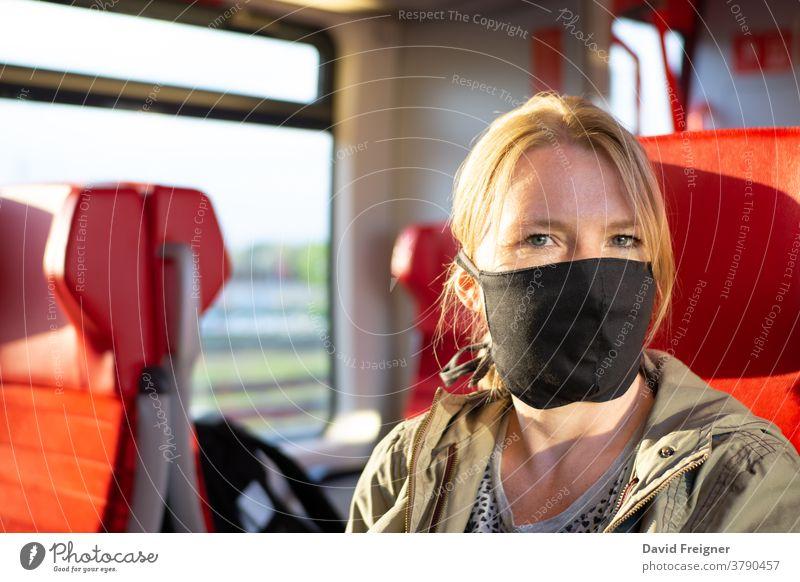 Frau, die in einem Eisenbahnzug reist und eine selbst angefertigte Gesichtsmaske trägt. Coronavirus und Reisekonzept Mundschutz U-Bahn reisen tragend Korona