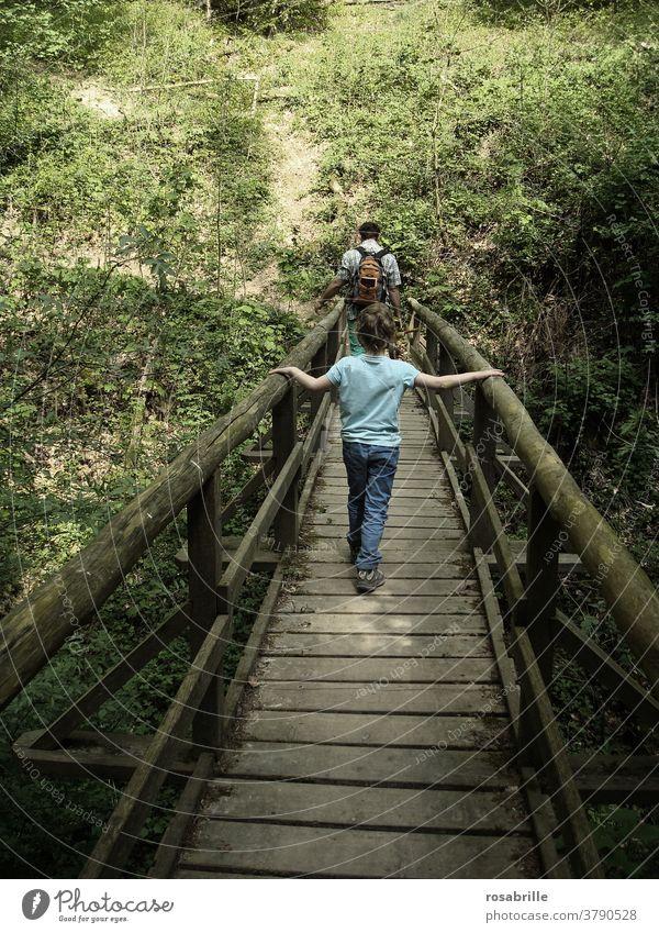 Zwischenräume | Kind geht hinter Vater über eine Holzbrücke Brücke folgen vertrauen festhalten gehen wandern spazieren miteinander nacheinander zusammen