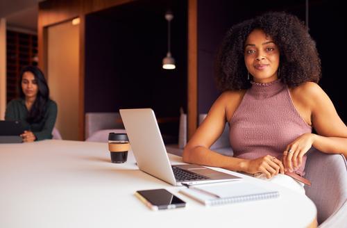 Portrait einer Geschäftsfrau mit Laptop bei einer sozial distanzierten Besprechung im Büro während einer Gesundheitspandemie Business Geschäftsfrauen Sitzung