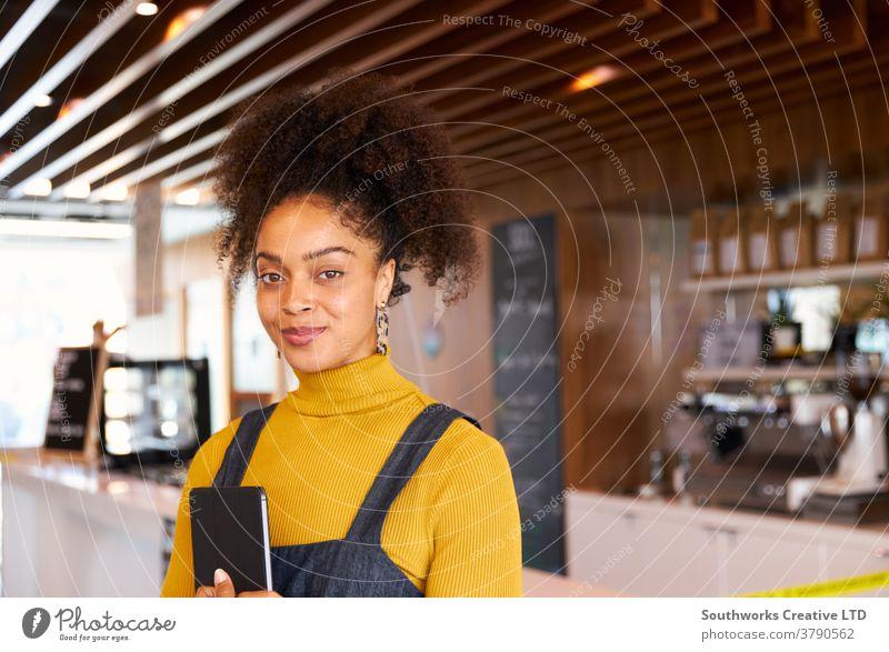 Porträt einer weiblichen Geschäftsinhaberin eines Coffee Shops in Maske, die während einer Gesundheitspandemie digitale Tabletten benutzt Business