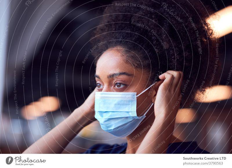 Ärztin in OP-Kleidung setzt während einer Gesundheitspandemie Gesichtsmaske unter Druck im geschäftigen Krankenhaus auf Arzt Krankenpfleger bürstet