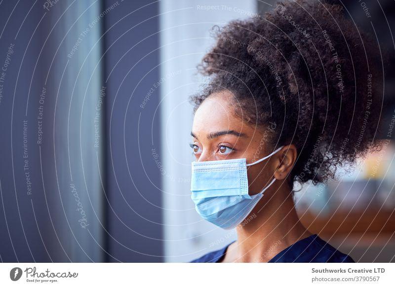 Weibliche Ärztin mit Gesichtsmaske und Kittel unter Druck im geschäftigen Krankenhaus während einer Gesundheitspandemie Arzt Krankenpfleger bürstet