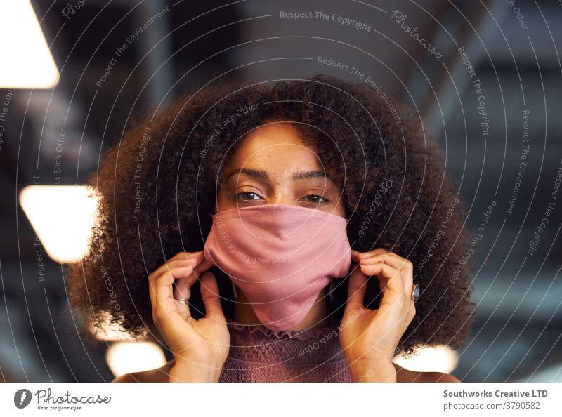 Porträt einer Geschäftsfrau, die während der Covid-19-Pandemie eine Gesichtsmaske in einem modernen Großraumbüro aufsetzt Business Gesichtsbedeckung ppe