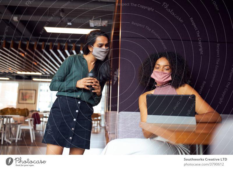 Geschäftsfrauen mit Masken, die während einer Gesundheitspandemie sozial distanzierte Treffen im Amt haben Business Sitzung Gesichtsmaske Gesichtsbedeckung ppe