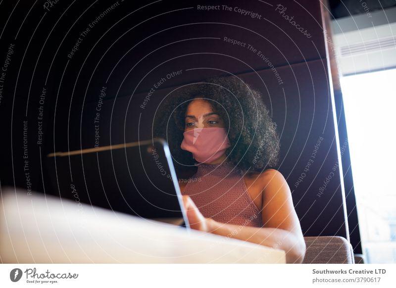 Geschäftsfrau mit Maske, die während einer Gesundheitspandemie in einer sozial abgelegenen Bürokabine arbeitet Business Gesichtsmaske Gesichtsbedeckung ppe