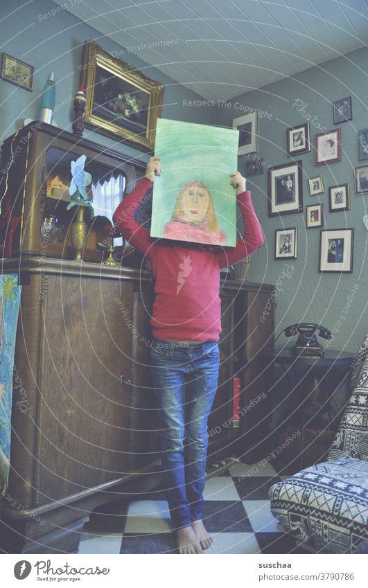 kind mit gemaltem selbstportrait vor dem kopf Kind Mädchen Selbstportrait Künstlerin Zeichnung Kopf Gesicht Papier Kunstwerk Wohnung wohnen altmodisch Bilder