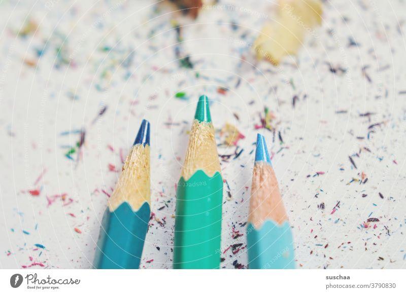 3 nicht ganz fertig gespitzte buntstifte Buntstift Farbstift blau grün Späne Holz Papier zeichnen Spitze Schreibstift Kreativität dreckig Künstler