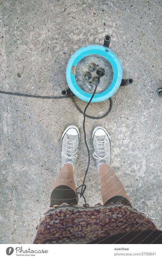 kabeltrommel mit stromanschluss auf asphalt, daneben die beine einer weiblichen person Kabeltrommel Stromanschluss portabel Stromstecker Stromkabel Anschluss