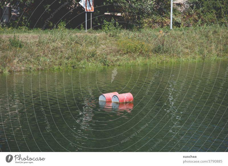 2 übel nach umweltverschmutzung aussehende schwimmende rote tonnen in einem gewässer Gewässer Wasser Fluss Ufer Flussufer Tonne rote Tonnen Umweltverschmutzung