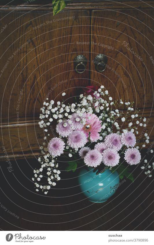 kleiner blumenstrauß in einer vase vor einem holzschränkchen Strauß Blumen Blumenstrauß Vase Pflückblumen hübsch Holz Holzschrank Dekoration & Verzierung Blüte