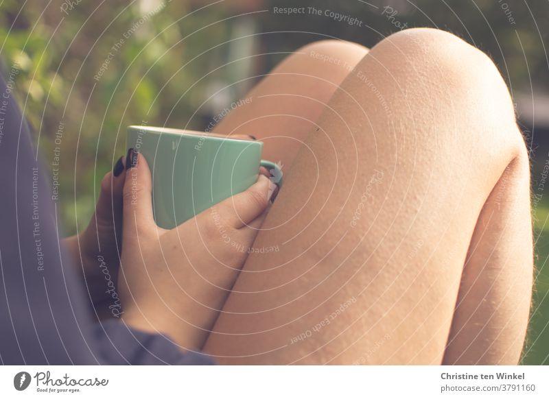 Junge Frau sitzt mit nackten aufgestellten Beinen und hält einen Kaffeebecher in ihren Händen mit den schwarz lackierten Fingernägeln. Seitliche Nahaufnahme mit schwacher Tiefenschärfe.