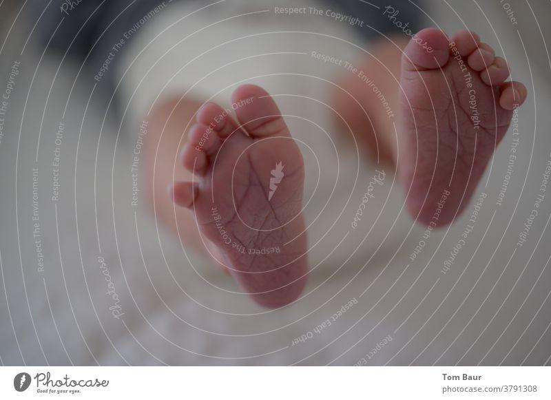 Nahaufnahme der Füße des Babys, während das Baby auf dem Wickeltisch liegt und seine Füßchen in die Luft streckt Babyfüße Füße hoch Beine Barfuß