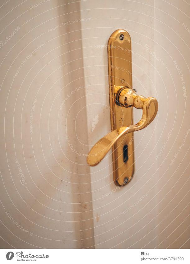 Weiße Tür mit goldenem Türbeschlag. Türklinke und Türschloss. weiß alt Altbau Eingang Schlüsselloch Griff Holztür