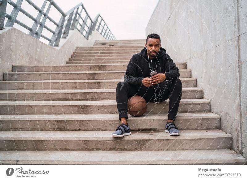 Sportler, der sein Mobiltelefon benutzt. Mann Läufer hören Kopfhörer Training Übung Lifestyle Erwachsener Gesundheit im Freien sportlich Typ laufen Mitteilung