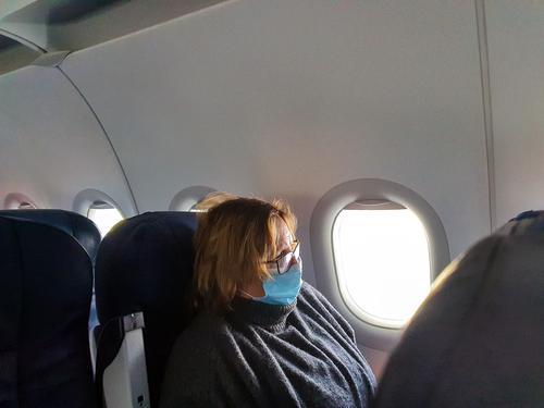 Alte ältere Frau reist mit medizinischer Schutzmaske für Covid-19, Reisen und Coronavirus-Konzept reisen Flug Mundschutz Flugzeug Tourist Virus Ausflug