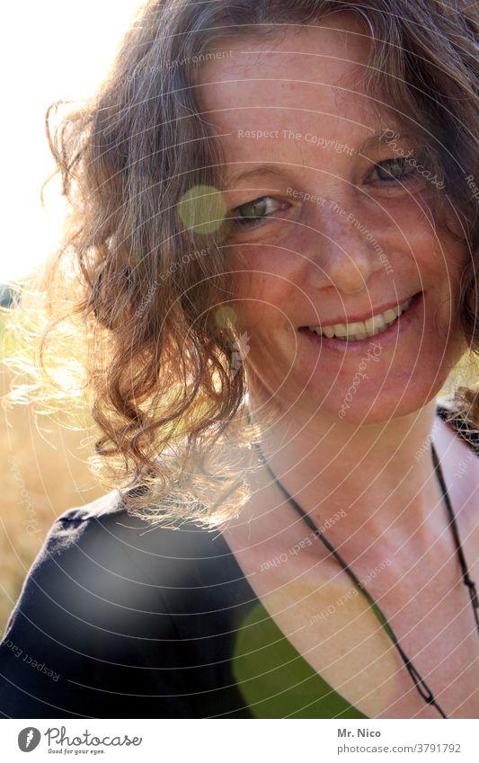 Portrait einer lächelnden Frau im Sonnenlicht Porträt Haare & Frisuren Blick sympathisch Ausstrahlung Freundlichkeit attraktiv Fröhlichkeit Wohlgefühl Kopf