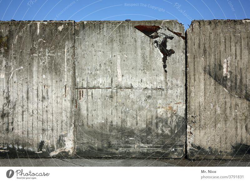 Eine in die Jahre gekommende Betonmauer vor blauem Himmel Mauer Wand Betonwand grau Blauer Himmel trist alt dreckig Endstation Ende trostlos Wiedervereinigung
