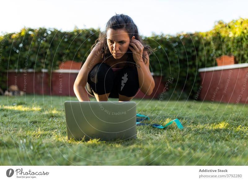 Sportlerin schaut sich während des Trainings ein Online-Tutorial an online Frau wählen pflücken Laptop benutzend Hinterhof Sommer Fitness Browsen Athlet