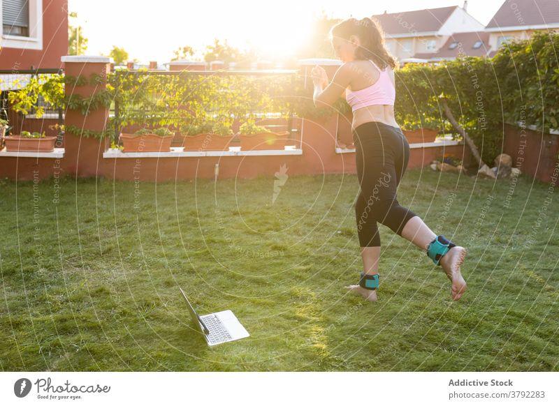 Schlanke Frau macht Übungen im Innenhof im Sommer Training Laptop online Tutorial benutzend Athlet Sonnenuntergang Sportbekleidung Gesundheit Fitness Internet