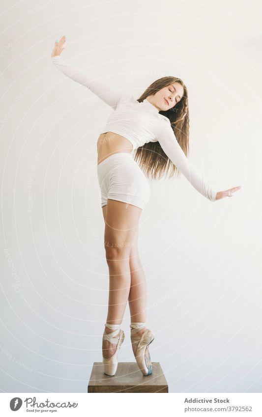 Schlanke Ballerina in Ballett-Pose auf Hocker Balletttänzer positionieren auf Zehenspitzen Schuh Gleichgewicht Anmut schlank Frau professionell Tanzen ausführen
