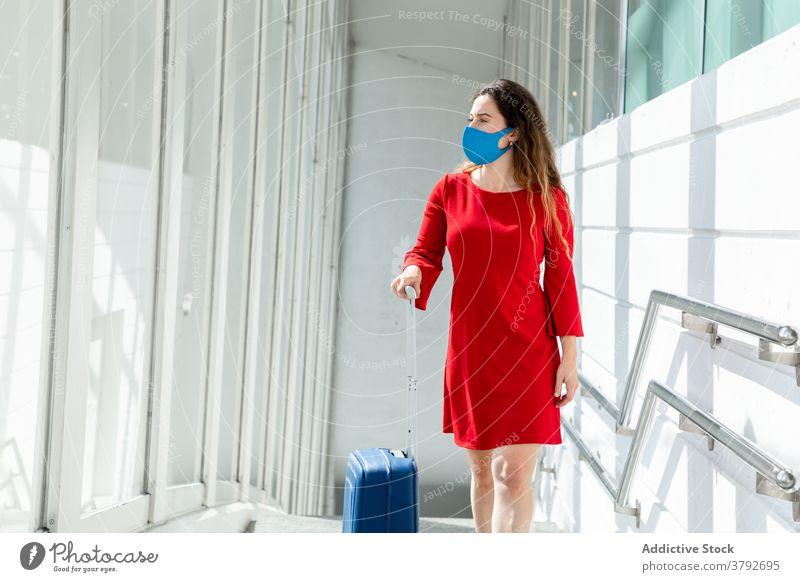 Reisende Frau mit Gepäck im Flughafen reisen warten Abheben Koffer Mundschutz Coronavirus Tourist Passagier Urlaub Feiertag Fenster Ausflug Reisender modern