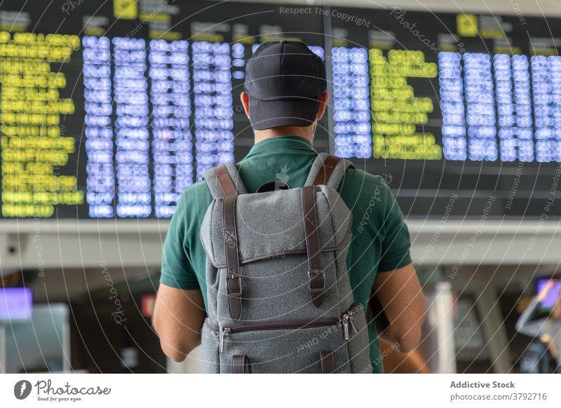 Unbekannter Mann mit Rucksack im Flughafen Abheben Holzplatte Zeitplan Reisender prüfen warten Tourist männlich international Urlaub reisen Ausflug Passagier