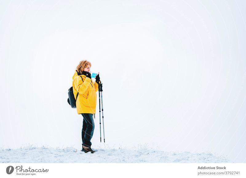 Wanderer mit Schutzmaske auf verschneitem Gelände stehend Trekking Reisender Mundschutz Coronavirus aktiv Schnee Berge u. Gebirge Rucksack Abenteuer COVID19