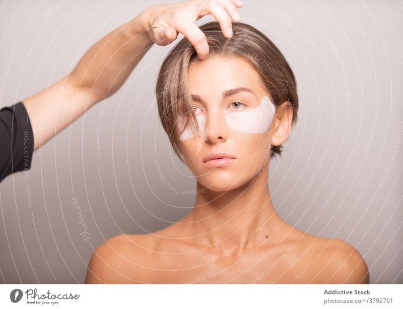 Anonymer Friseur, der die Haare eines weiblichen Modells im Studio einstellt Behaarung ausrichten Atelier vorbereiten Photo-Shooting Vorschein Stil trendy