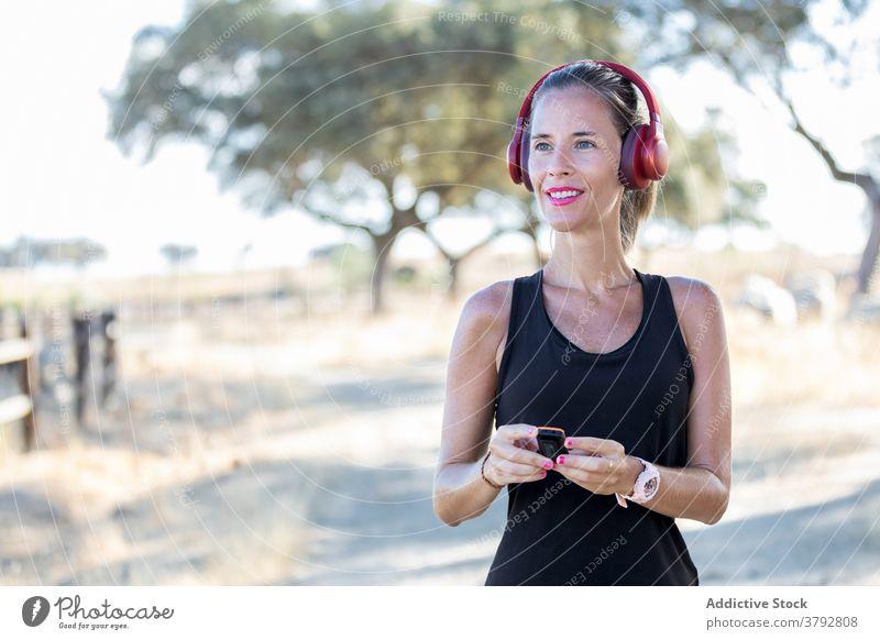 Frau benutzt MP3-Player und Kopfhörer im Park Apparatur zuhören mp3 Spieler benutzend Klang Melodie Audio Podcast Musik unterhalten Gesang jung Konzentration
