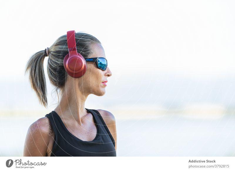 Frau mit Kopfhörern vor dem Training im Park Sportlerin zuhören Fitness Musik schlank Vitalität Athlet passen Aktivität sportlich Sportkleidung Sportbekleidung