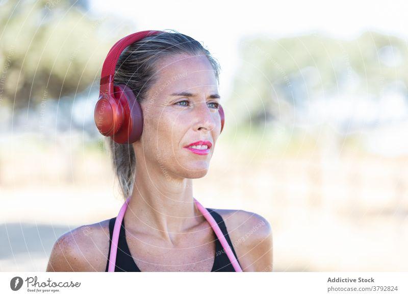 Fröhliche Sportlerin mit Kopfhörer im Park stehend positiv zuhören Fitness Gerät passen Inhalt aktiv Training Musik schlank Vitalität Athlet Aktivität sportlich