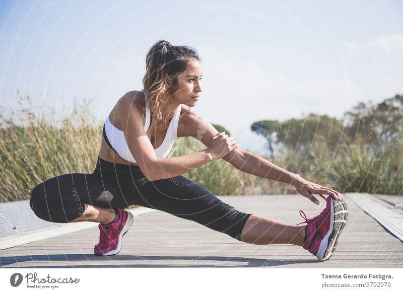 Attraktive Frau macht Dehnungsübungen im Freien Sportkleidung sportlich Mädchen rennen Herz Fitness Joggen Lifestyle Sportbekleidung Park See Sonne springend