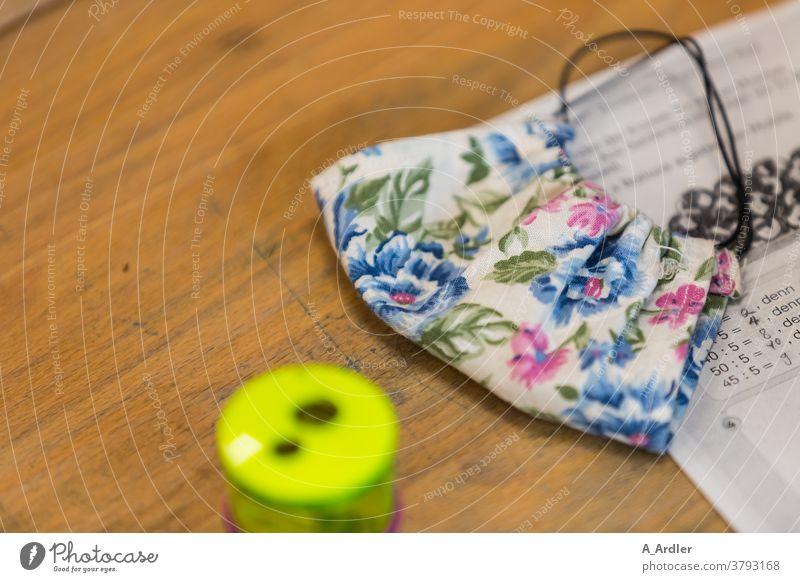 Mund und Nasenschutz für Kinder in der Schule Corona Covid-19 MNS Masken Pandemie Unterricht Klasse Klassenraum Schultisch Tisch Tischplatte Ohne Personen weiß