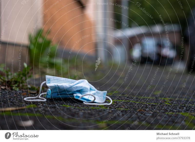 Weggeworfener Mund-Nasen-Schutz (Einweg) gegen Corona auf einem Bürgersteig Mundschutz Maske Pandemie Infektionsgefahr Coronavirus Krankheit Virus Corona-Virus