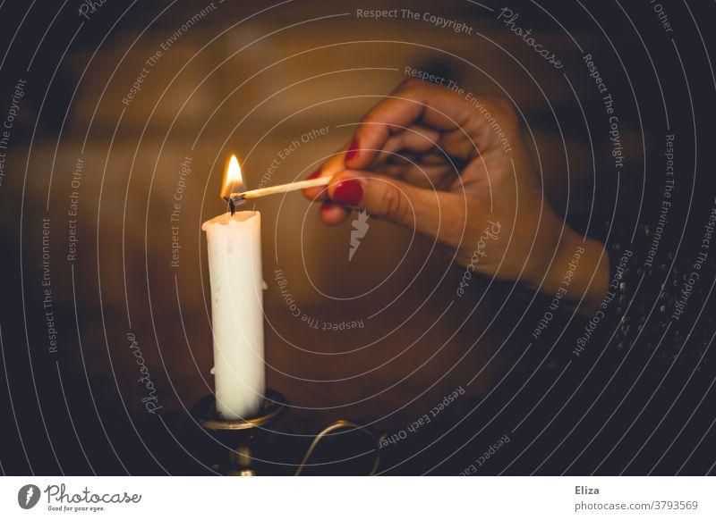 Eine Frau zündet zuhause eine weiße Kerze mit einem Streichholz an anzünden gemütlich Kerzenschein Romantik brennen stimmungsvoll Wärme Licht