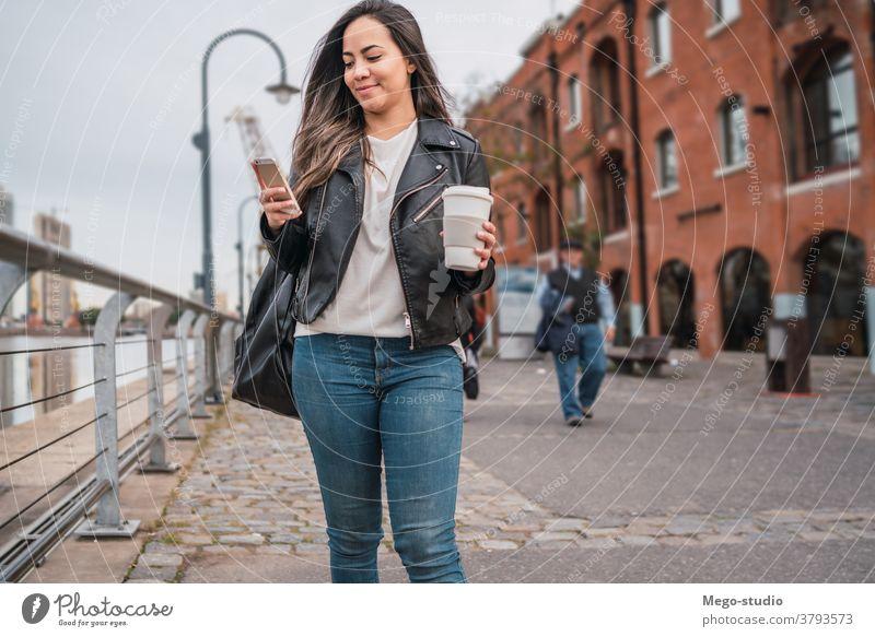 Junge Frau benutzt ihr Telefon. Straße Smartphone Großstadt Mobile Menschen urban klug Funktelefon Text jung SMS Nachricht im Freien Erwachsener online Internet